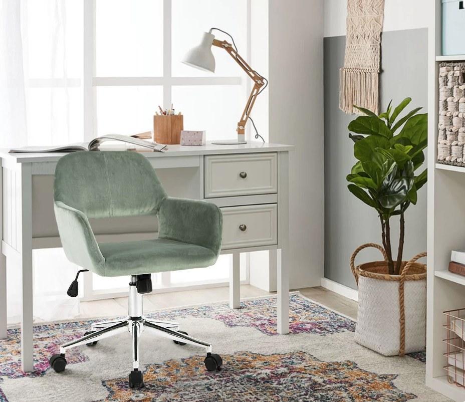 Green velvet wheeled office chair in home office