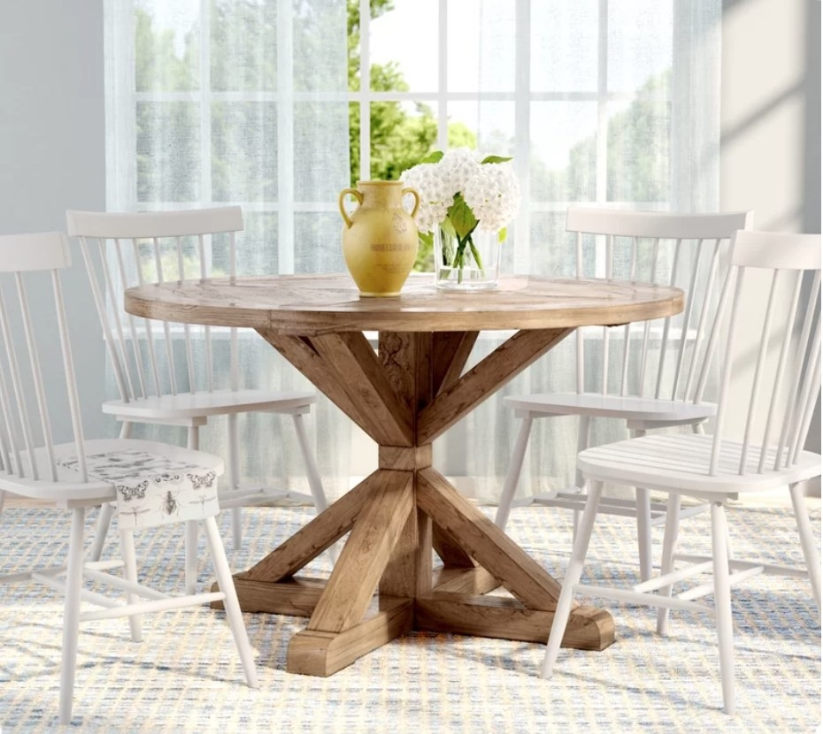 Round wooden table surrounding by white chairs