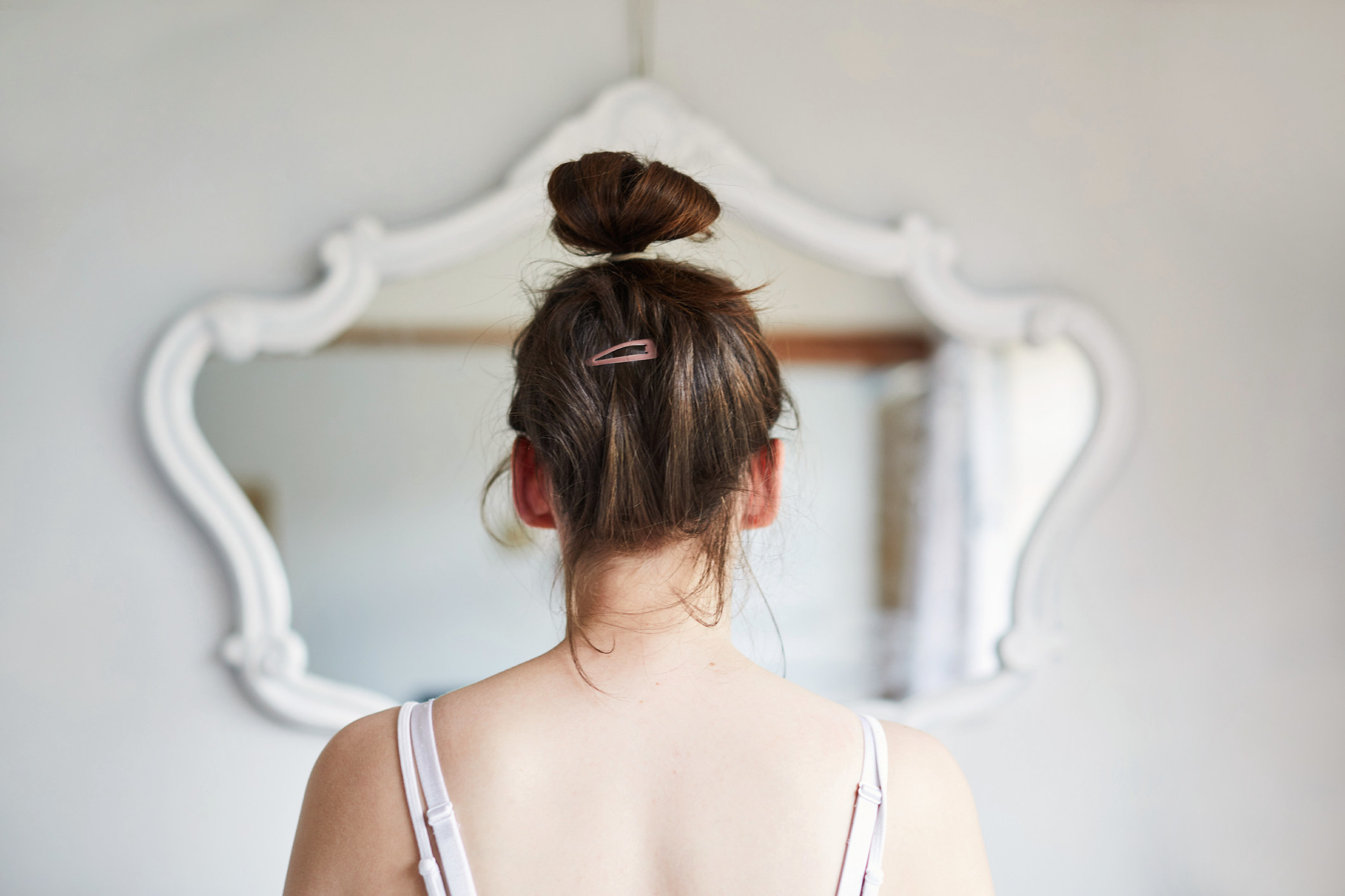 View from behind of a Woman looking her reflection in the mirror