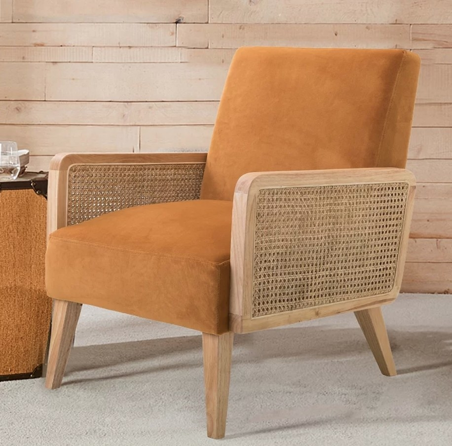 Orange accent chair with rattan arms and wooden legs