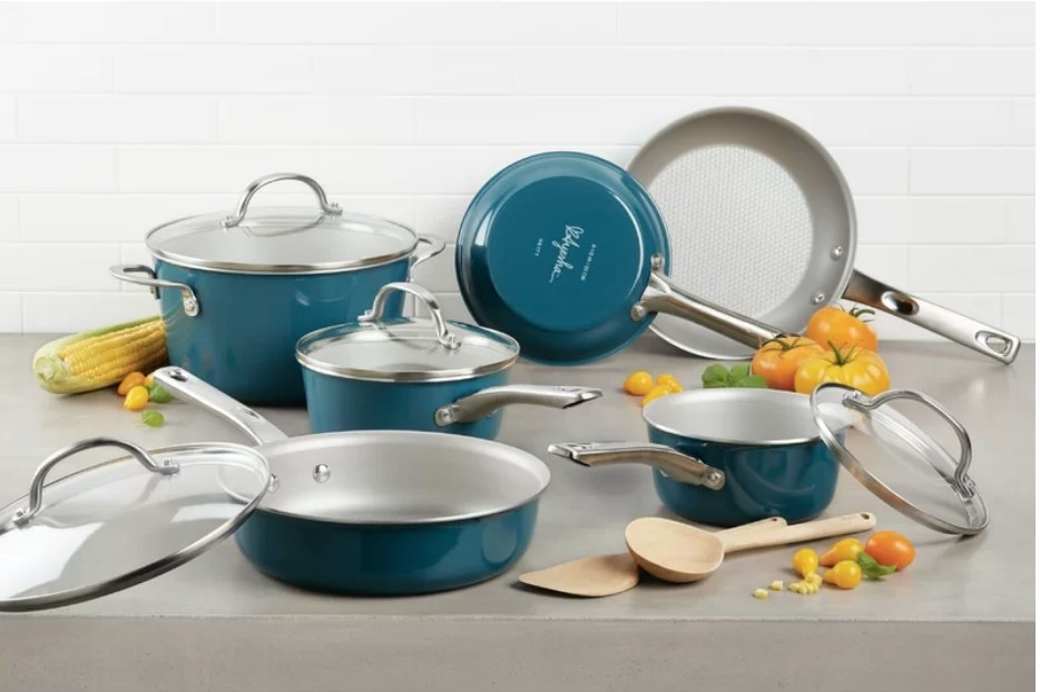 A 12-piece, non-stick cookware set in teal with a wooden spoon and wooden sauté paddle