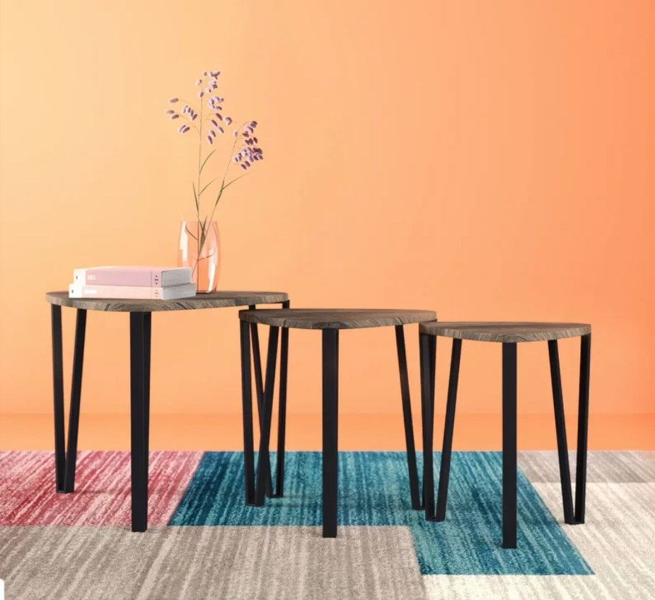 Three wooden nesting tables with black legs