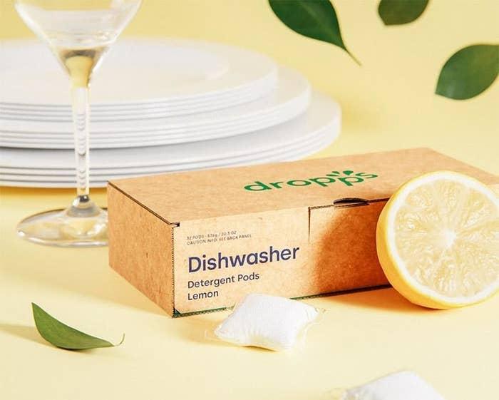 the lemon dishwasher pods displayed next to a sliced lemon