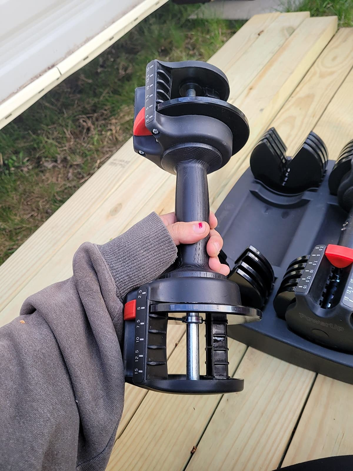 reviewer holds a black adjustable dumbbell in their hand
