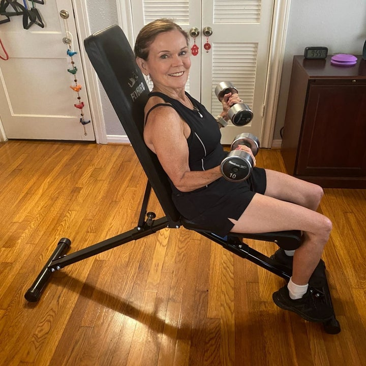 reviewer sits on black adjustable weight bench while doing bicep curls