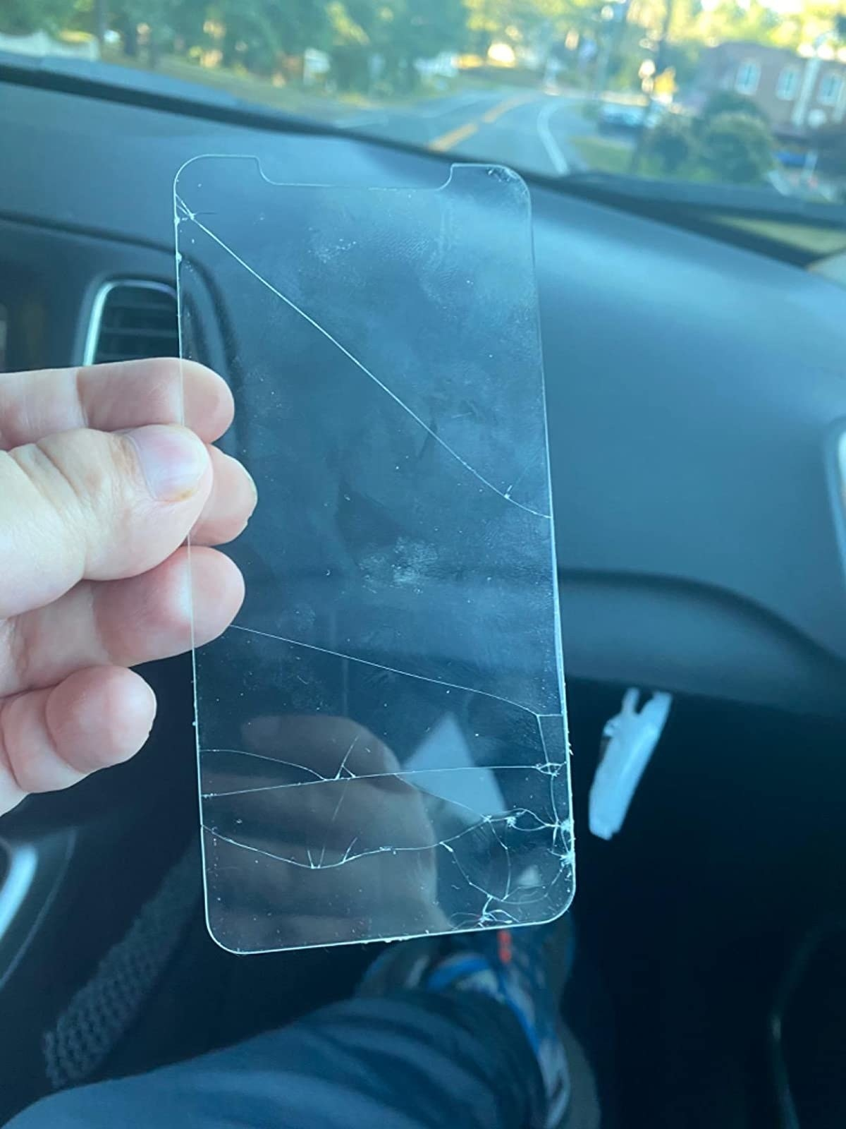 a hand holding a cracked screen protector