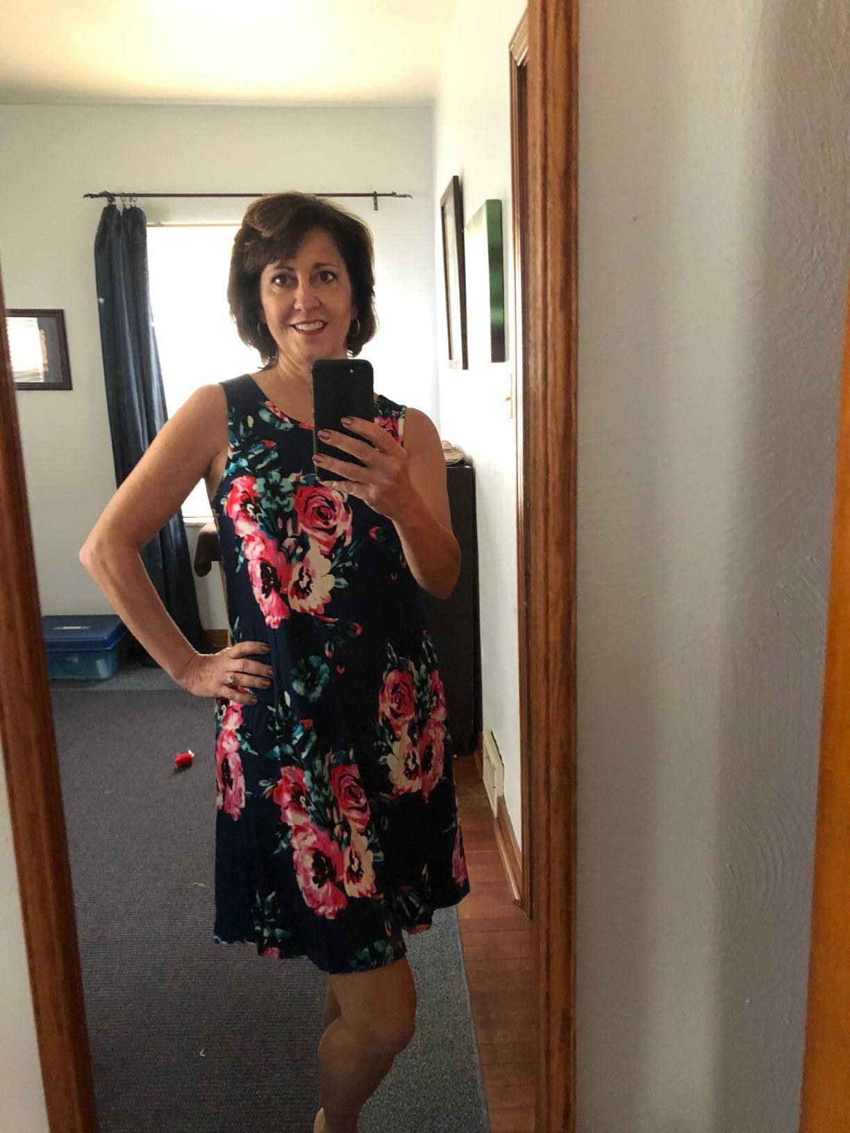 reviewer in navy above-the-knee dress with illustrated pink and teal flower print