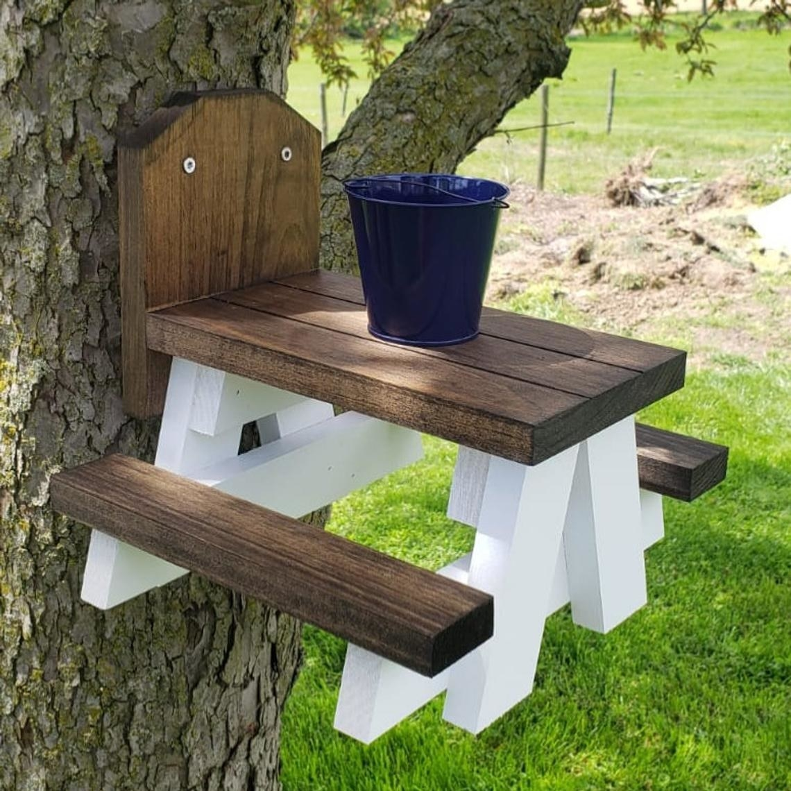 Farmhouse picnic table mounted to a tree trunk with a metal bucket on the table top