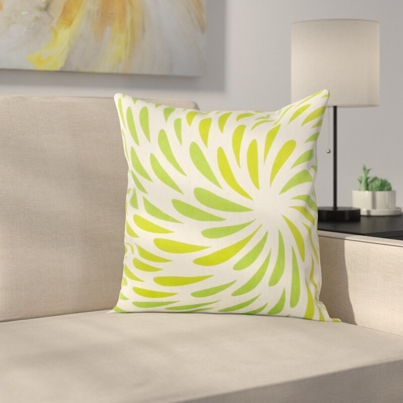 The pillow, in different shades of green