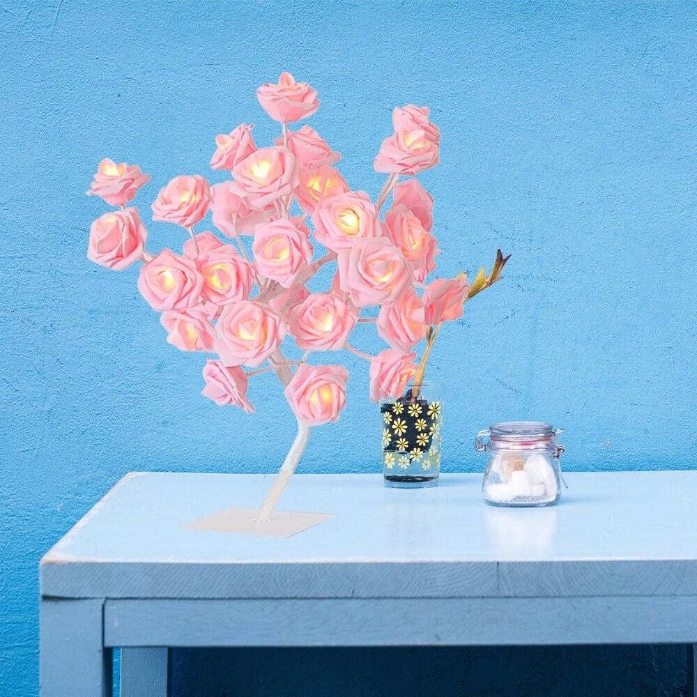 The lamp, which looks like a gathering of pink roses, on a blue table