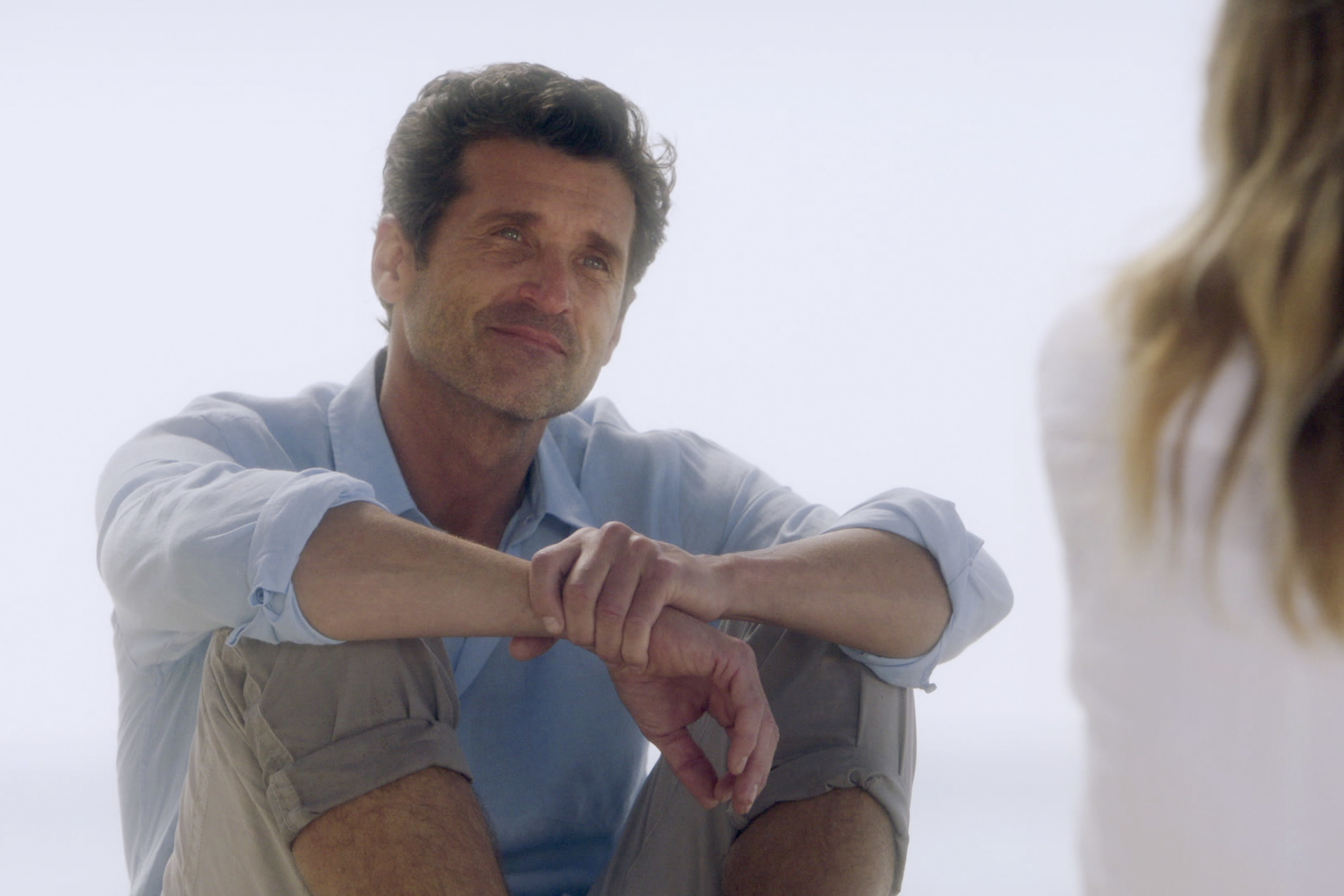 Dempsey sits with his arms on his knees in Grey's Anatomy