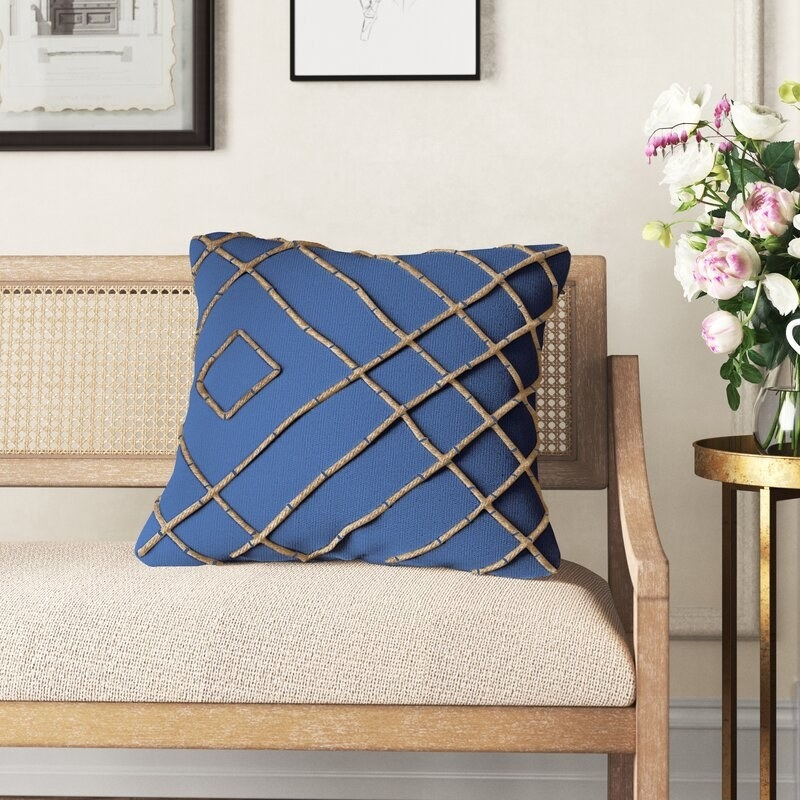 the pillow in blue on a white and tan couch bench