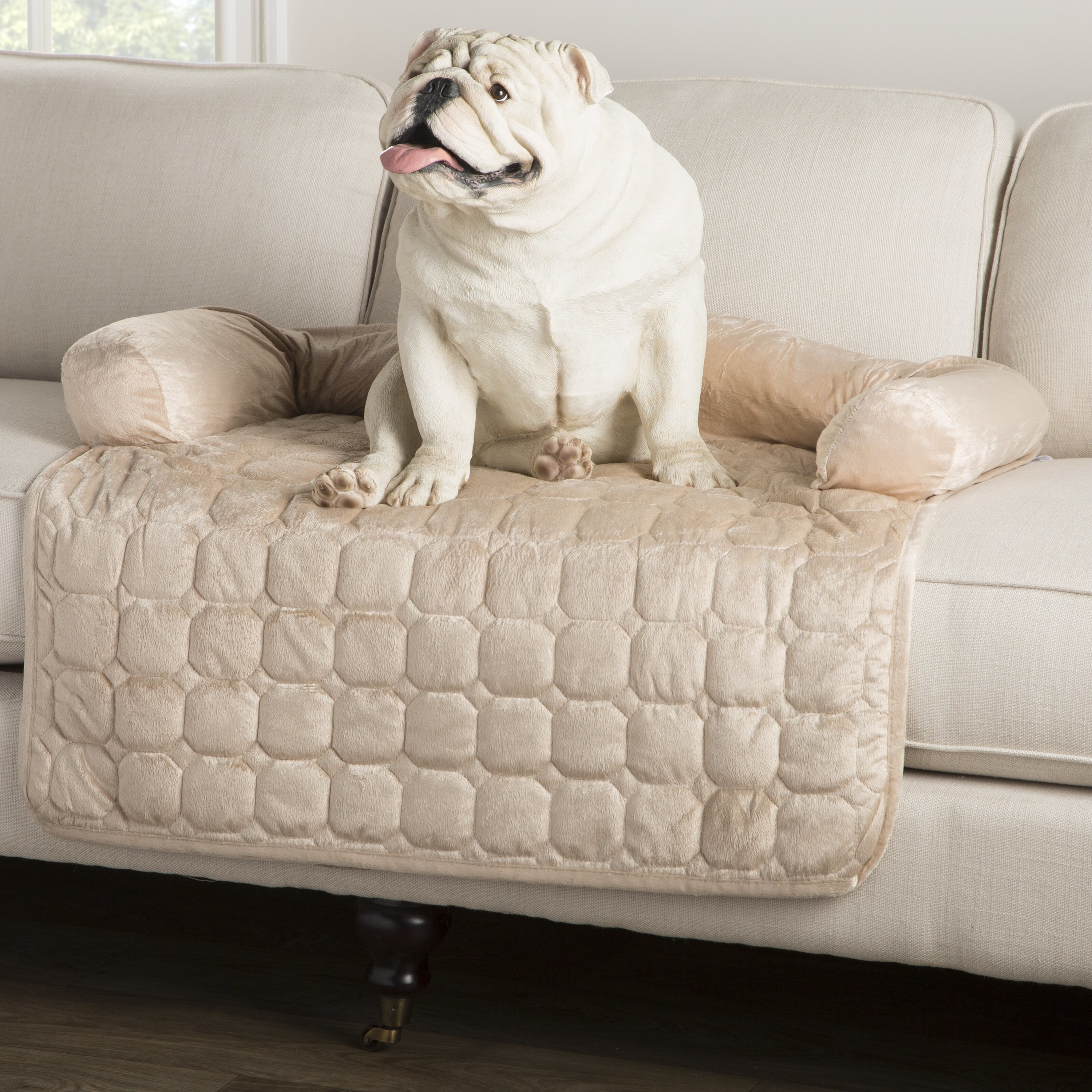 The furniture cover on a white couch with a bulldog resting on it