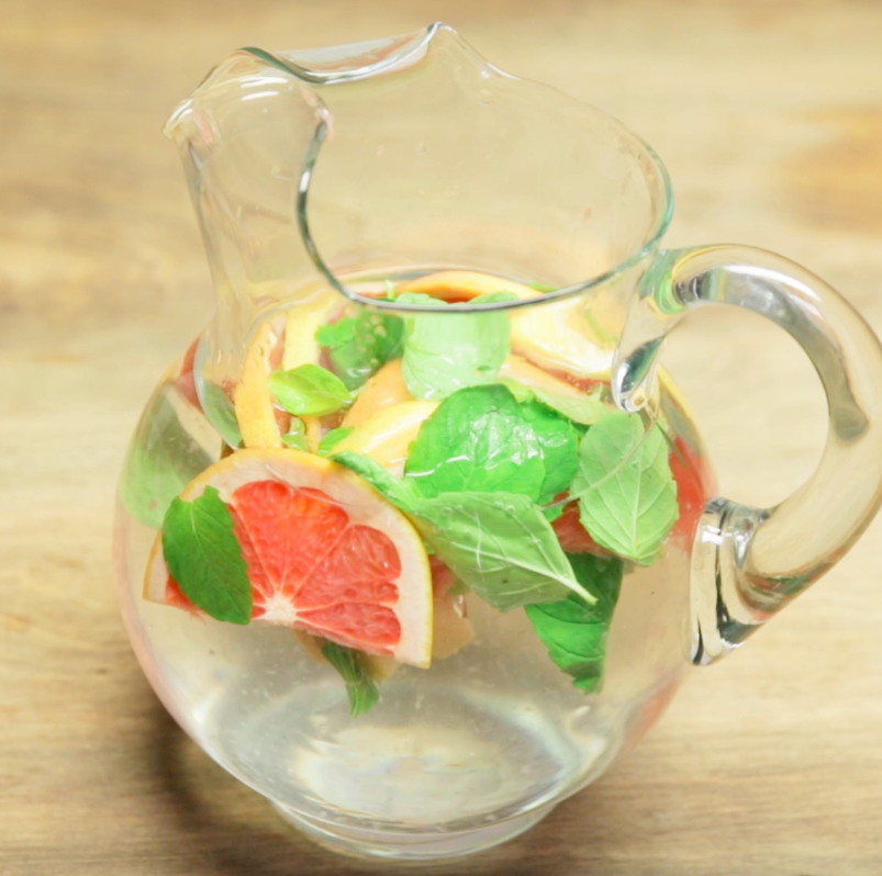 a pitcher of water with grapefruit and mint
