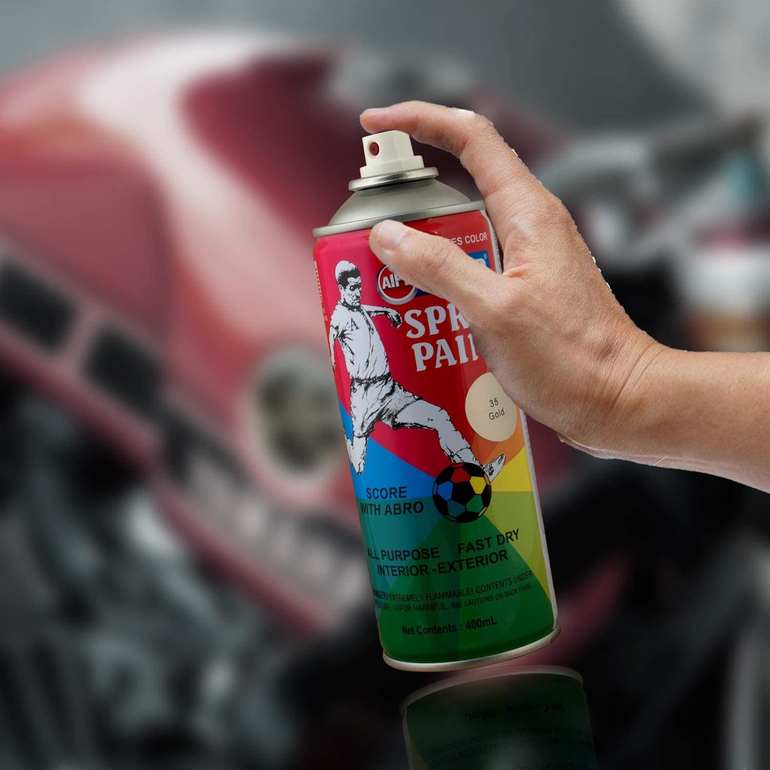 A hand holding the can of paint.