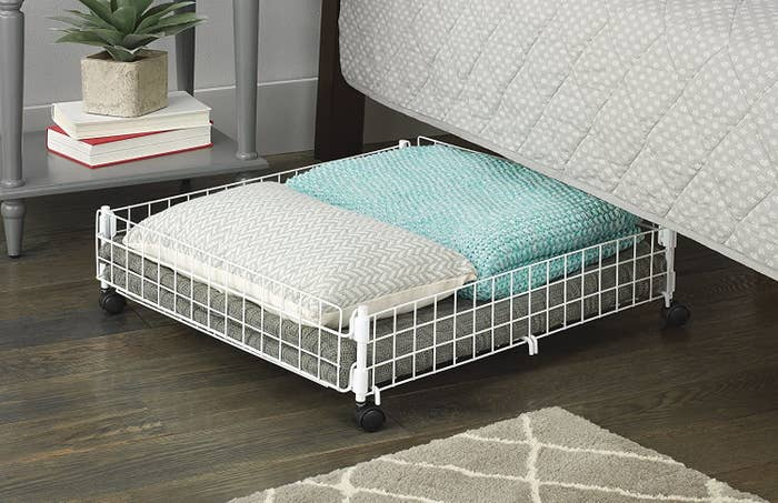 The wheeled basket with pillows and blankets under a bed