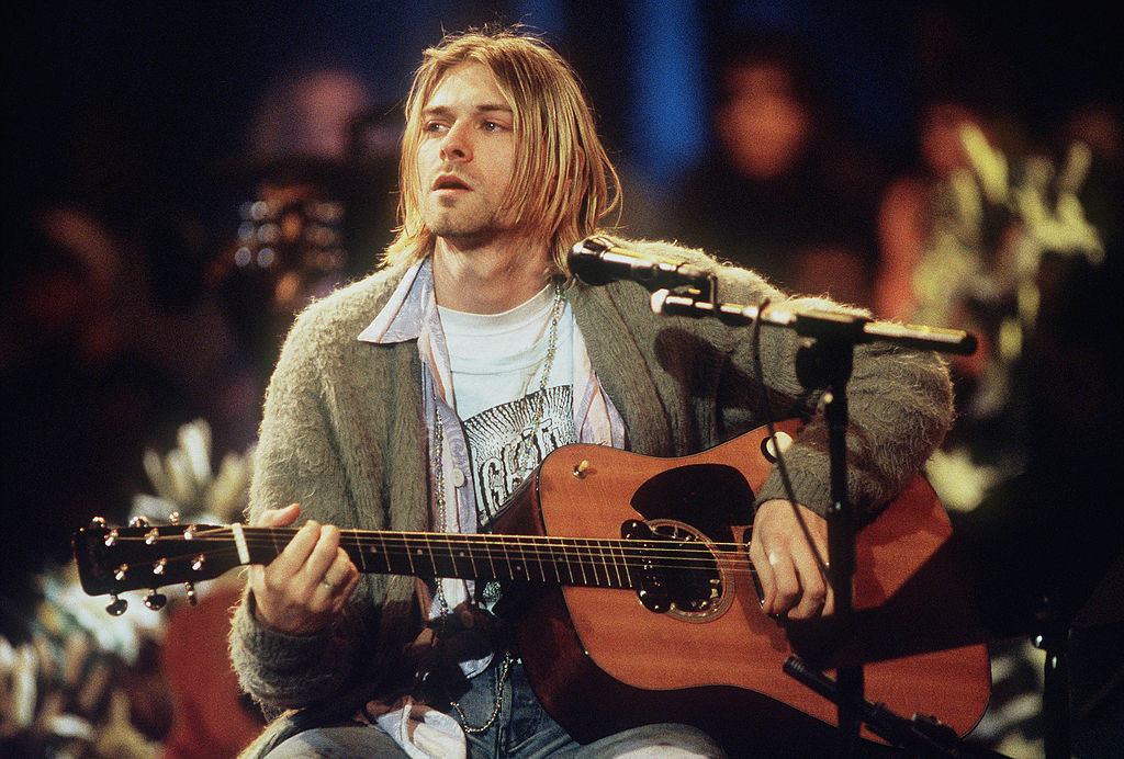 Kurt sitting with a guitar at a microphone