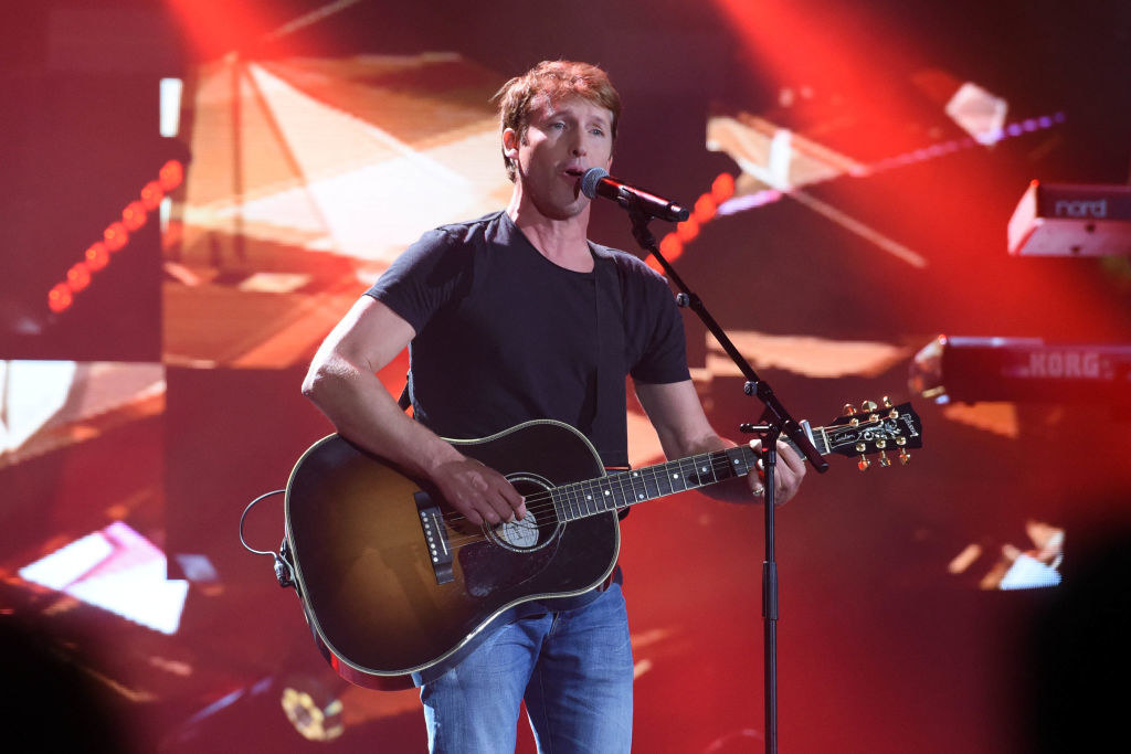 James wearing jeans and a T-shirt and singing and playing guitar onstage