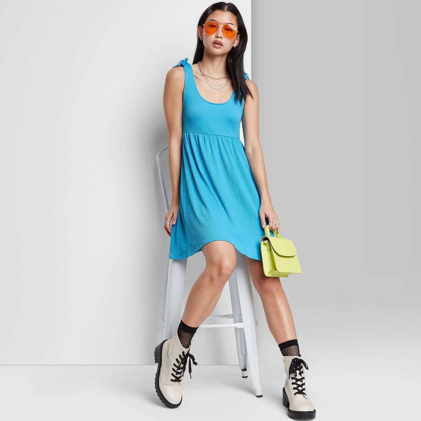 Model wearing blue sleeveless dress, stops above the knee