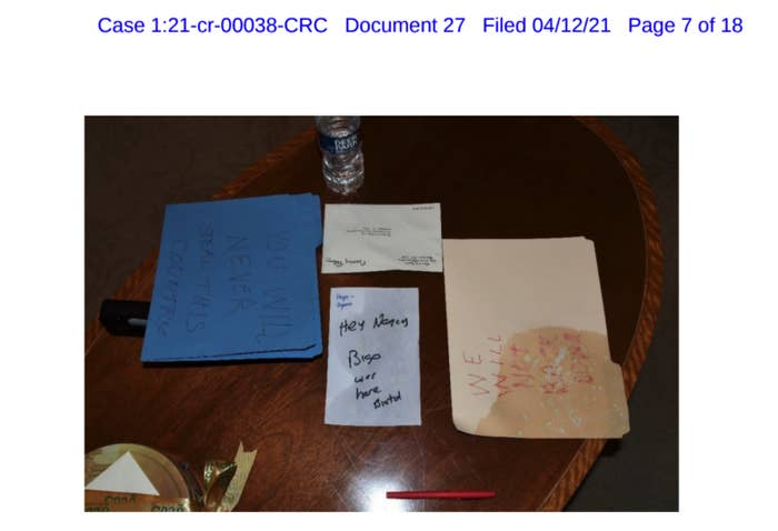 An image of illegible handwritten notes on a desk is seen in a court document