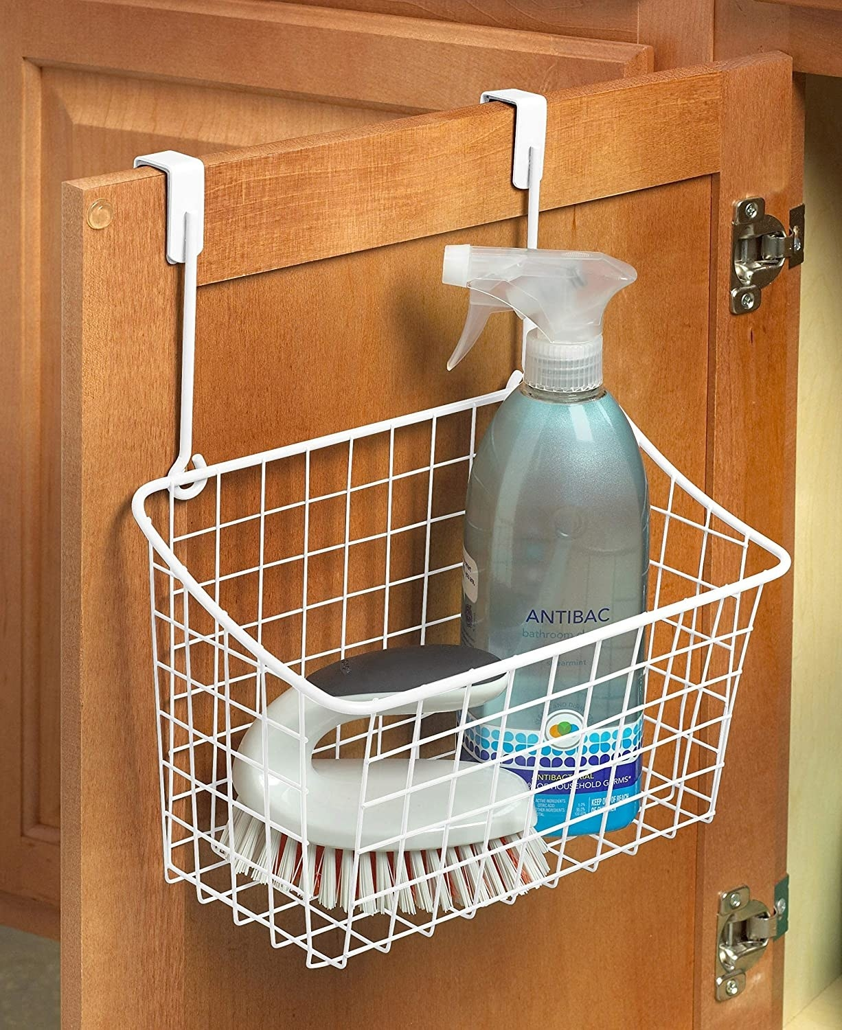 a basket hanging off of a cabinet with cleaning supplies in it