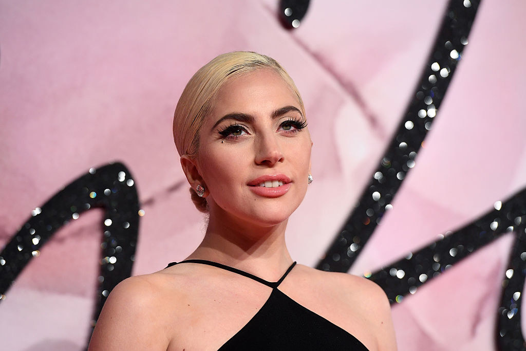 Lady Gaga with her hair pulled back and wearing a black thin-strap halter outfit