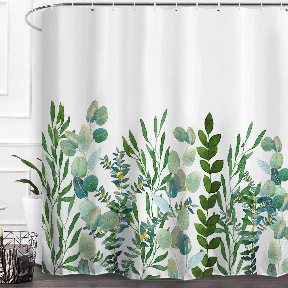 the shower curtain with plants printed on it