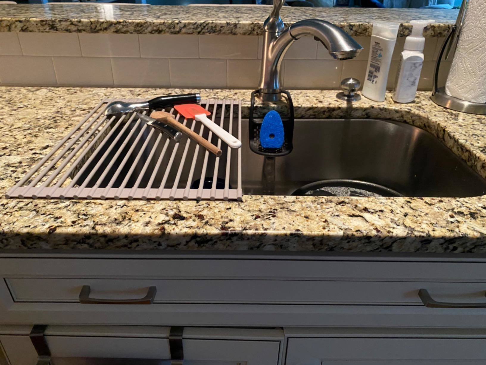 the rack with utensils on one side of a large sink