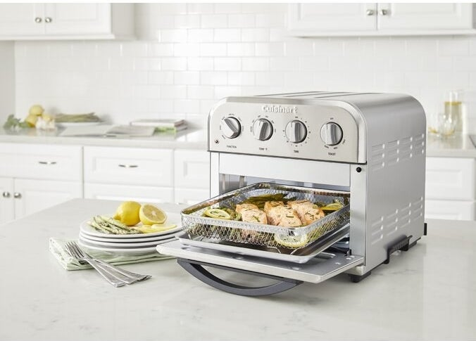 The oven, which has a pull-out tray and basket attachment for cooking