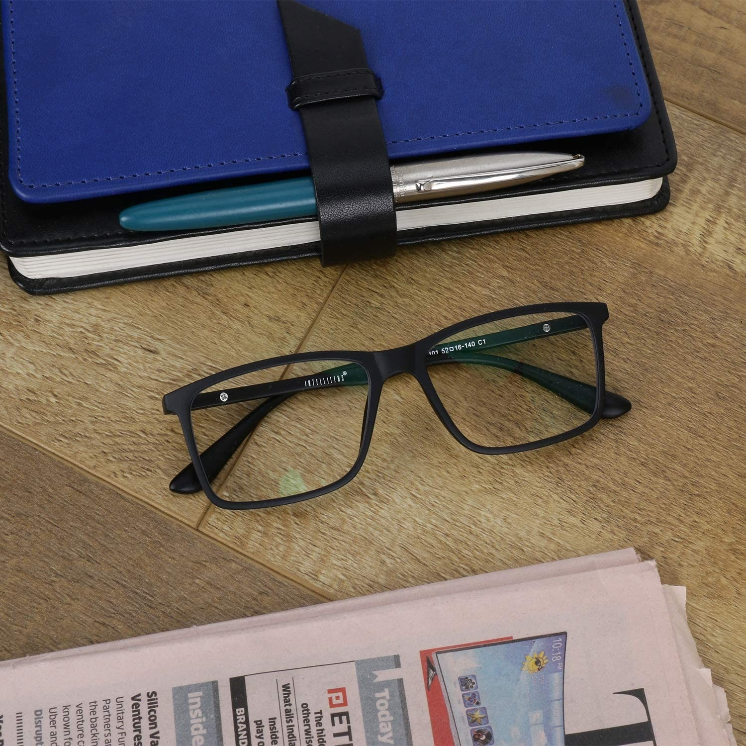 Glasses on a table beside a newspaper and a notebook.