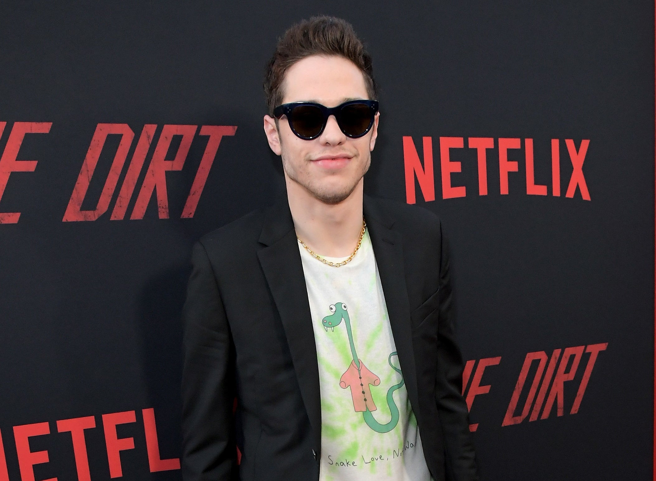 Pete wears sunglasses and a graphic tee with a suit jacket