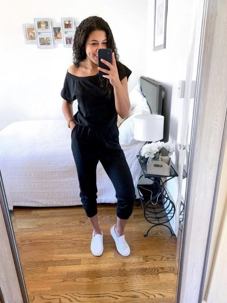a reviewer wearing the jumpsuit in black with white shoes