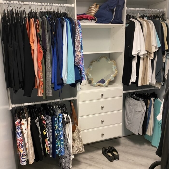 A reviewer photo of the closet system, which has a central drawer area, four hanging rods, and three shelves