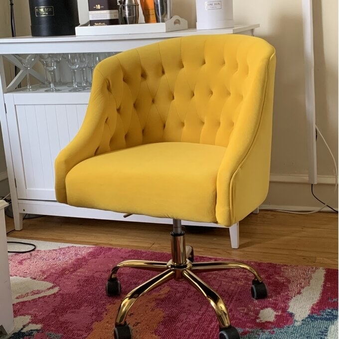 The chair, which has a gold swivel base, in yellow