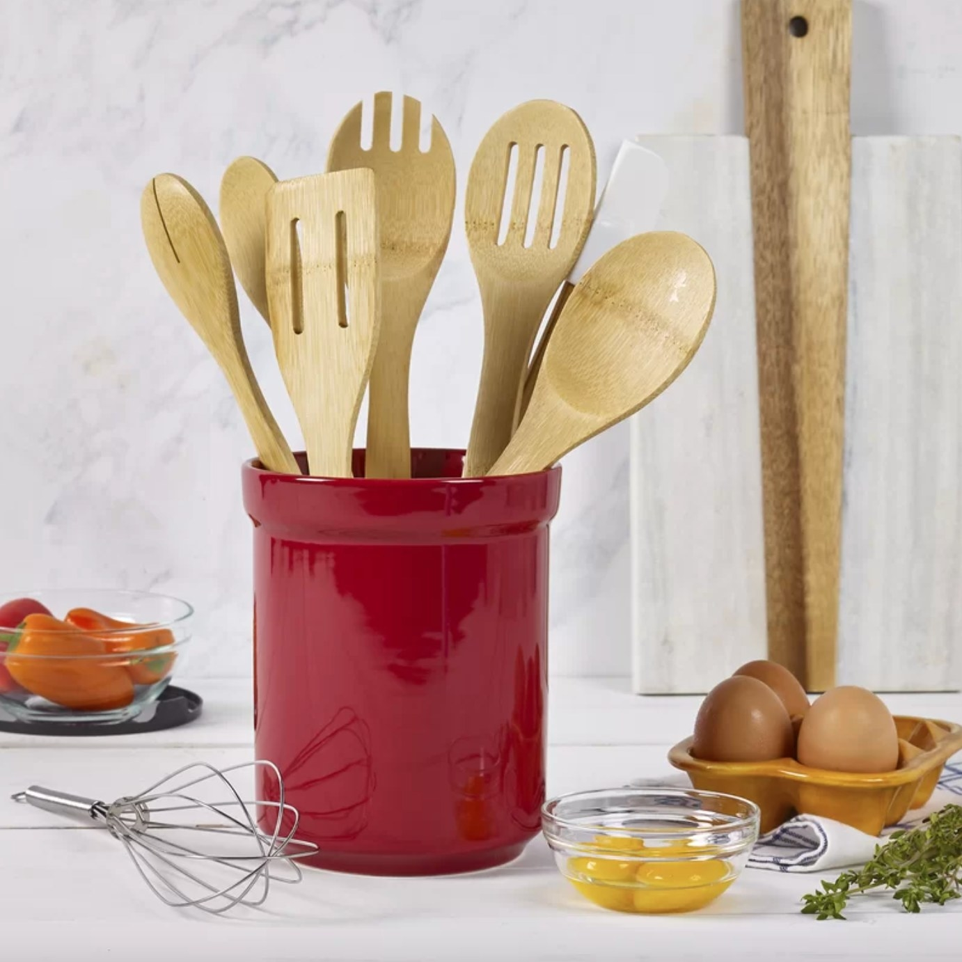 The kitchen tool set in red holding wood utensils