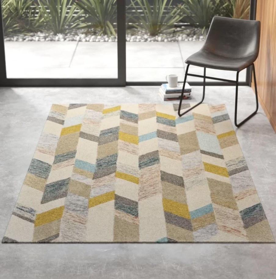 A handmade, rectangular, tufted area rug with a geometric design displayed in a living room