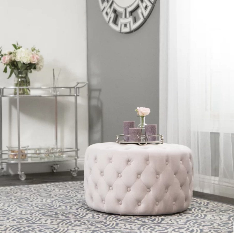 A cream, tufted cocktail ottoman with a tray of candles and flowers on top of it, displayed in a living room