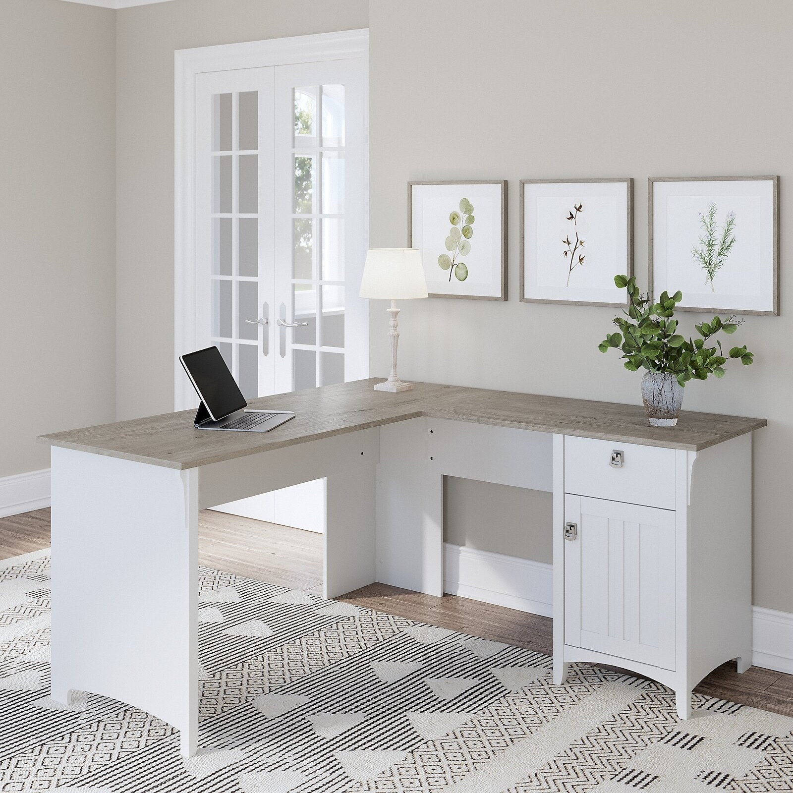 The desk, which is L-shaped and has a cabinet/ drawer storage area in one leg, in white
