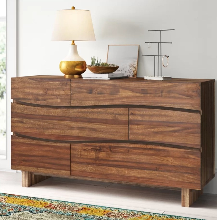 A brown wooden 6-drawer dresser with a beautifully curved panel design