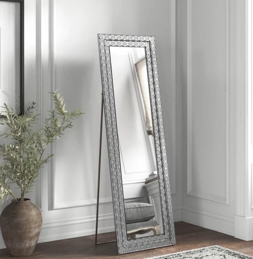 A glamorous, metal-framed full-length mirror