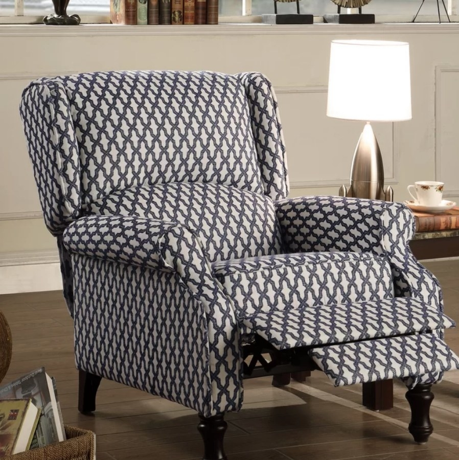 A blue and white, manual wing recliner chair with removable cushions