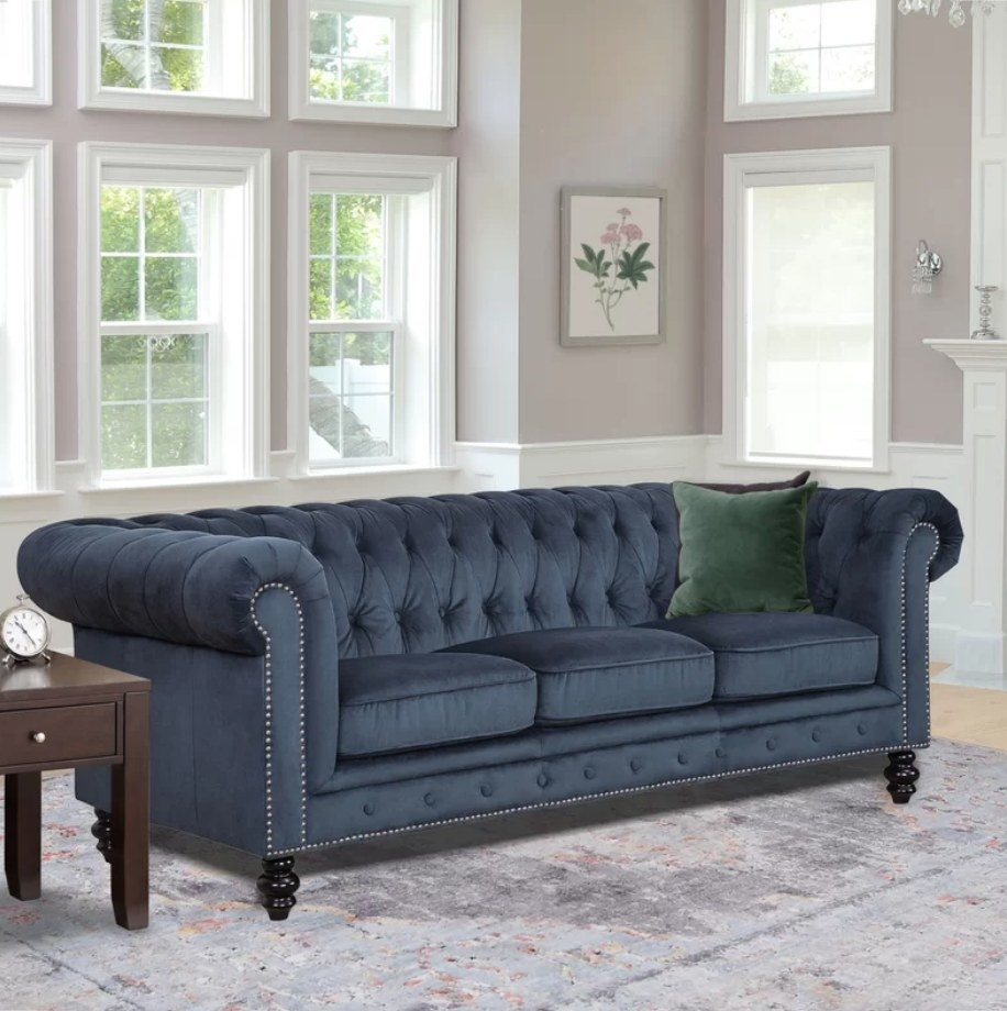 A navy blue chesterfield sofa with rolled arms displayed in a living room