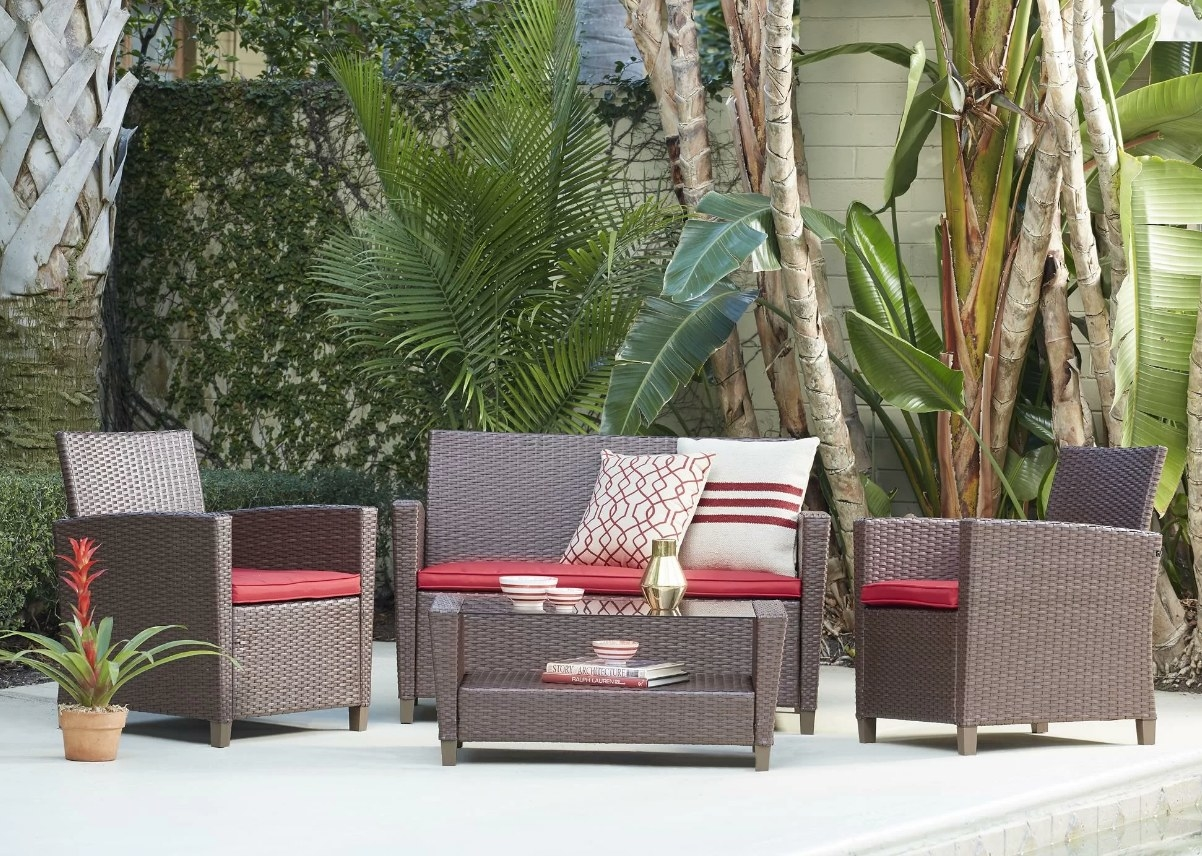 A brown rattan outdoor patio set that includes two chairs, one table, and one loveseat paired with red cushions