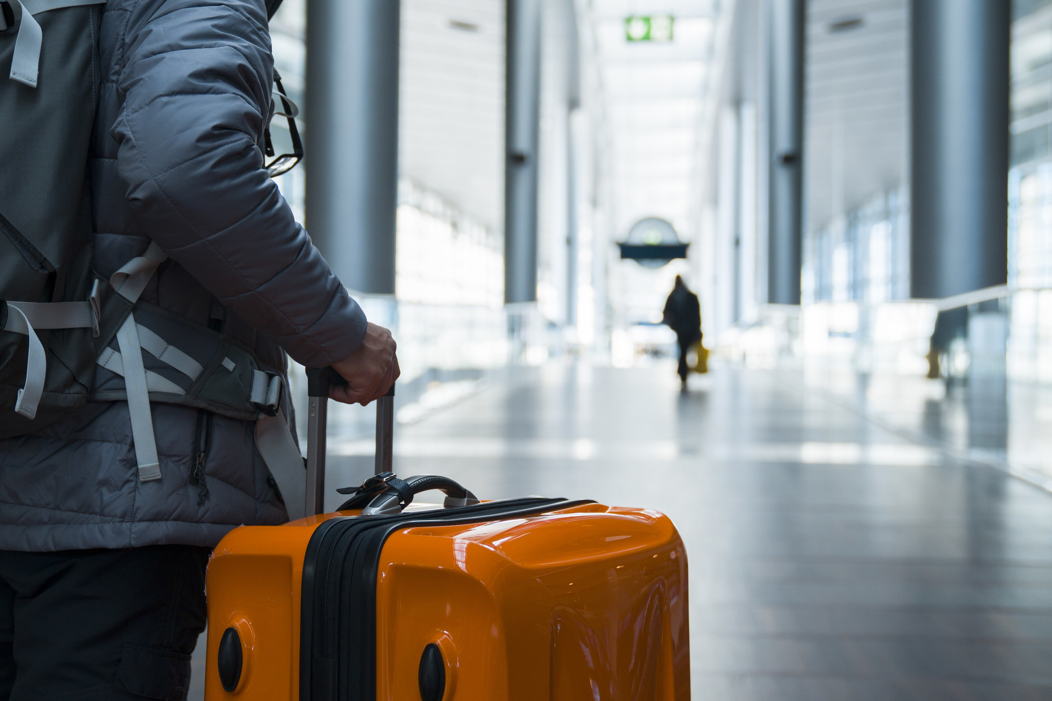 Someone walks with their suitcase at airport terminal