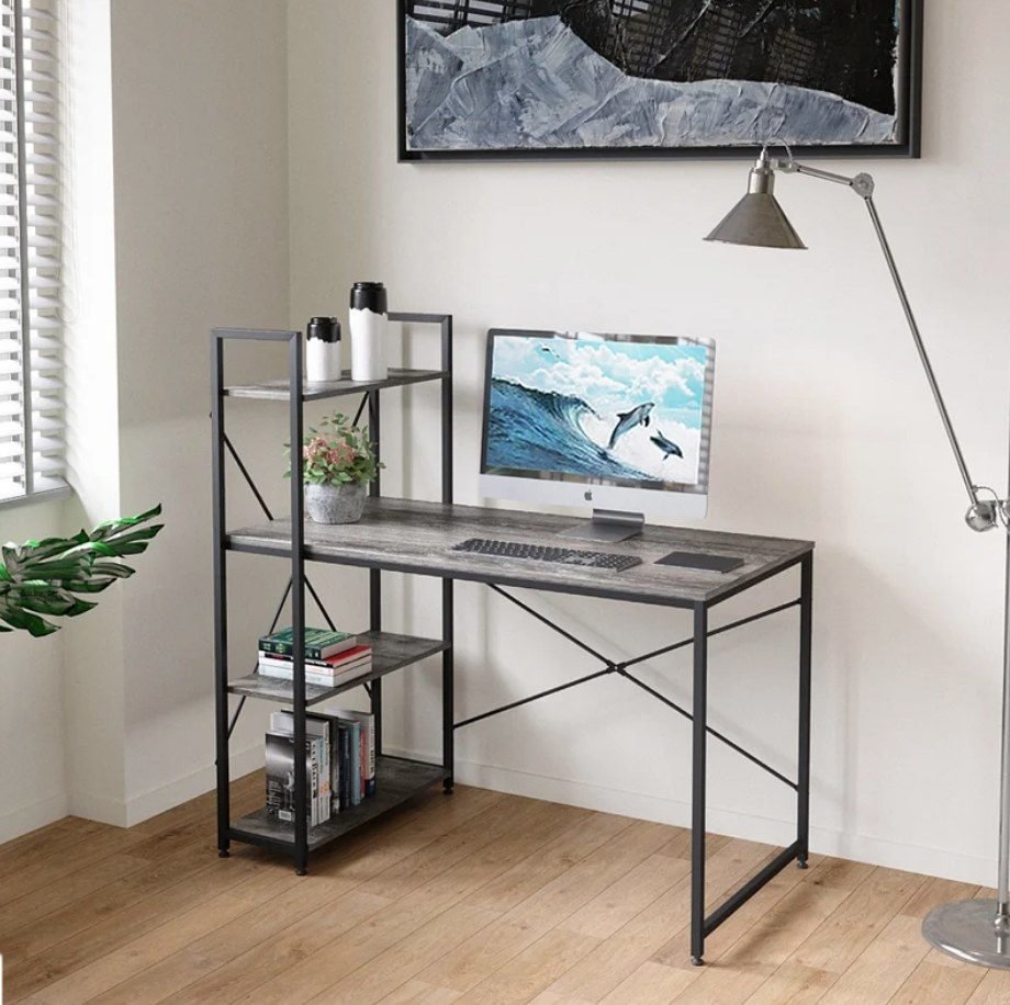 Gray desk with black detailing and shelf on lefthand side