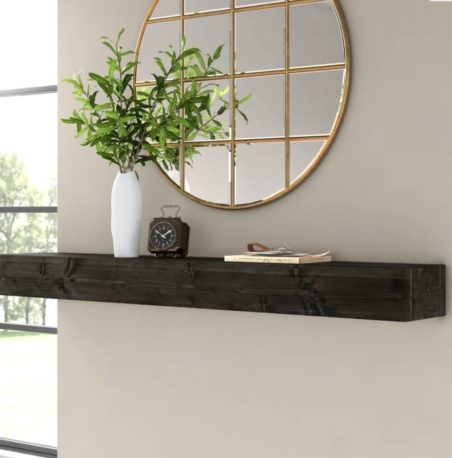 Black floating shelf with white planter, clock and book on it