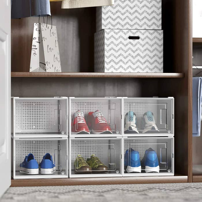 A set of six shoe containers stacked neatly in a closet