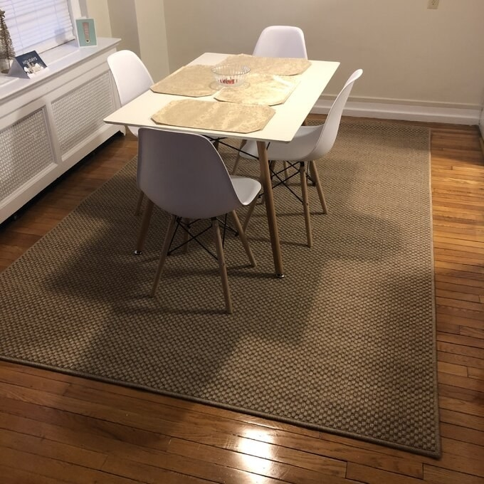 The rug, which is rectangular and tan