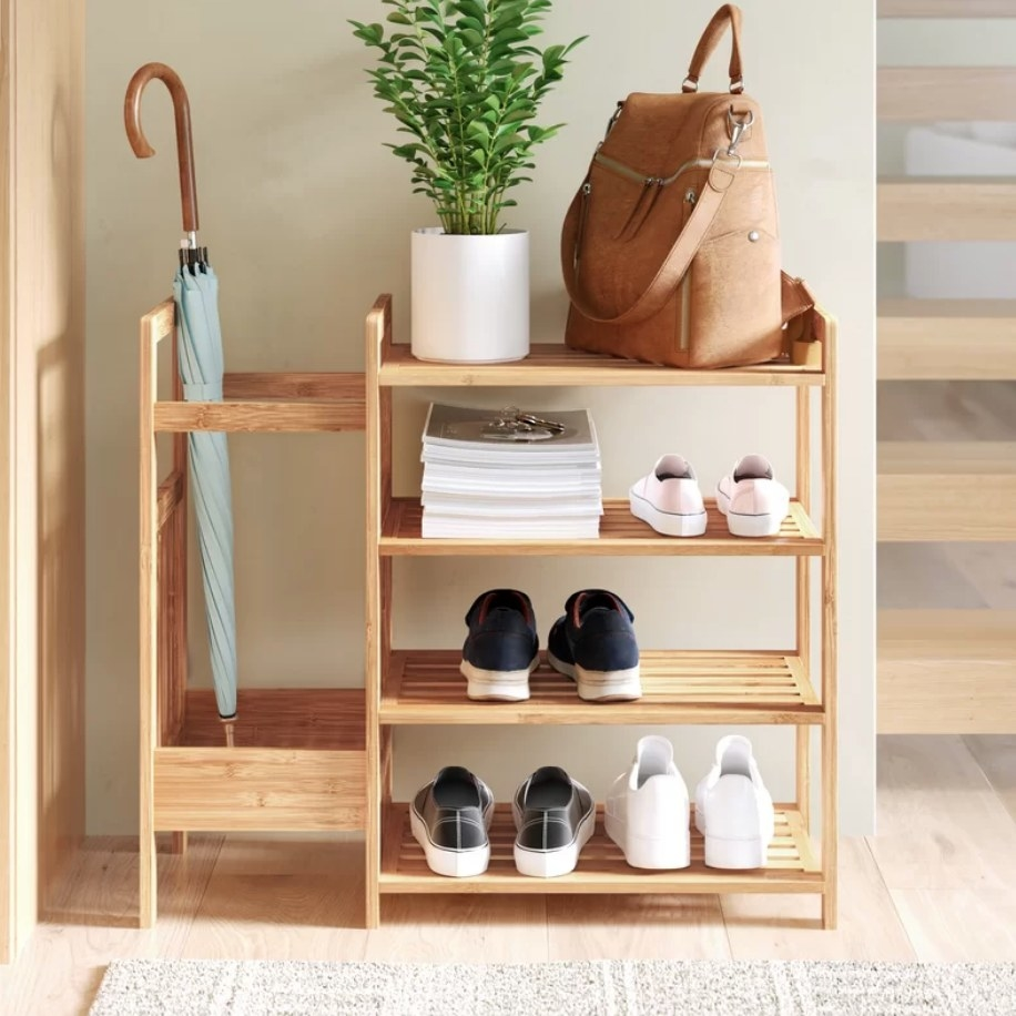 Bamboo shoe rack with umbrella on the left side panel and shoes on the first four shelves and bag/planter on the top