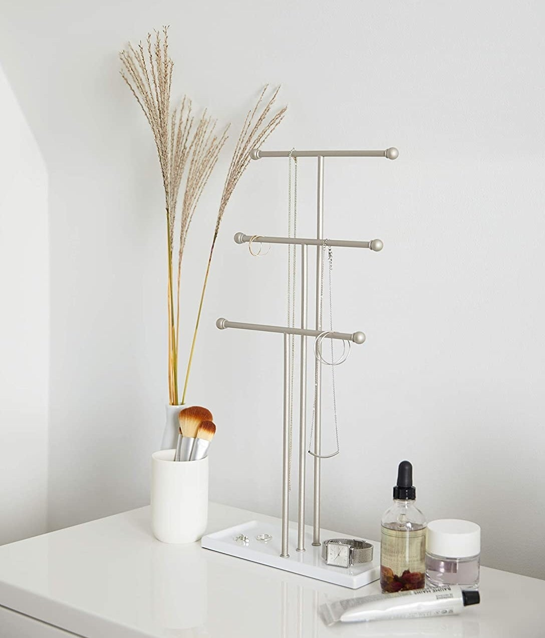 The jewelry stand on a minimalist vanity with necklaces hanging off of it